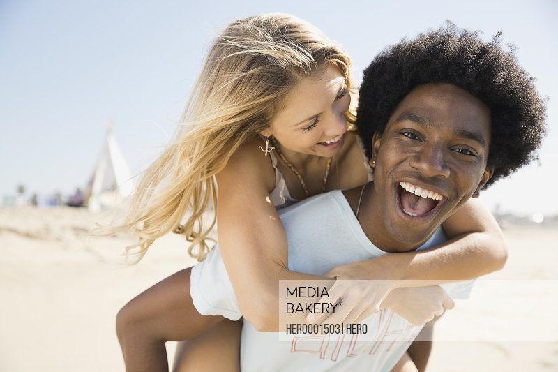 Portrait of excited man piggybacking girlfriend