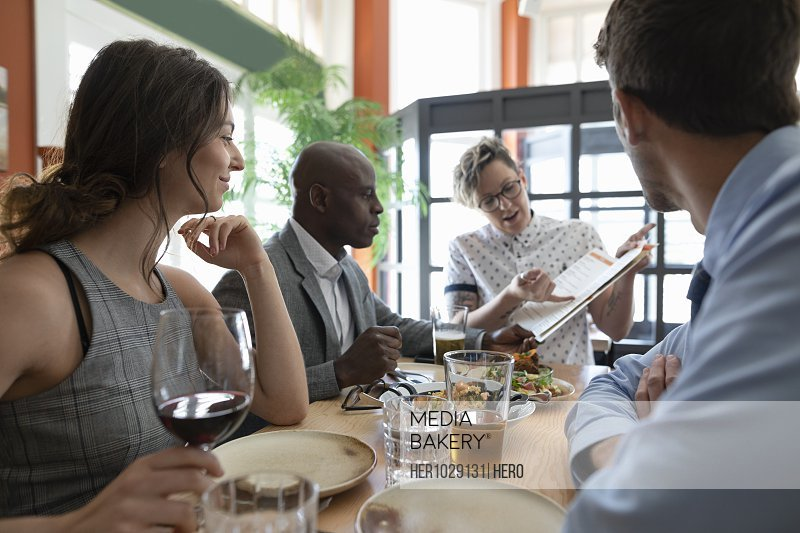 Waiting staff showing business colleagues menu in restaurant