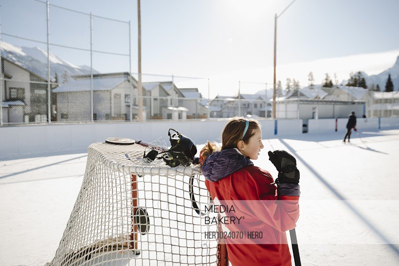 Girl playing outdoor ice hockey, resting at goal