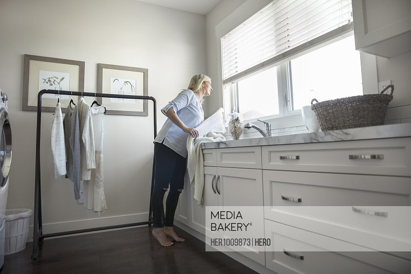 Woman folding laundry at counter in laundry room