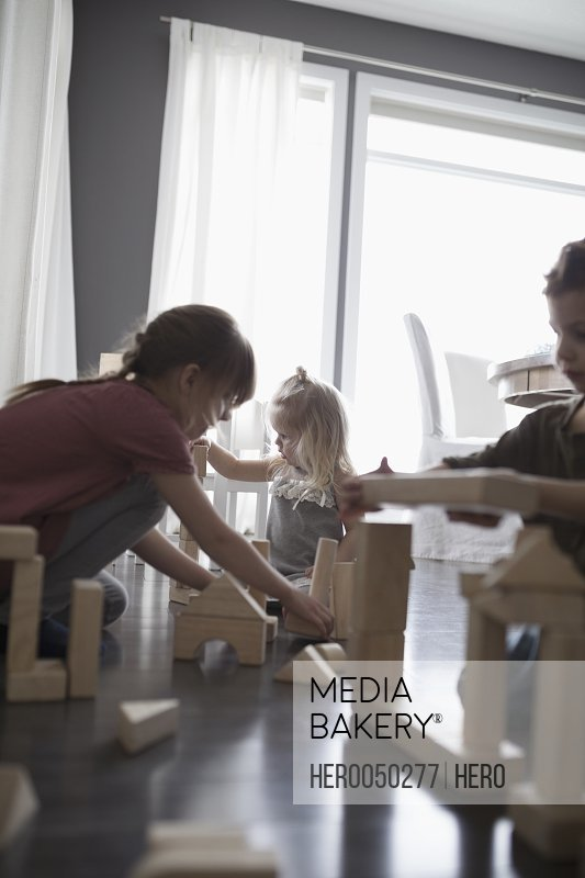 Brother and sisters playing with wood building blocks