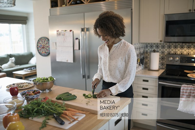 Woman cooking, cutting vegetables in kitchen