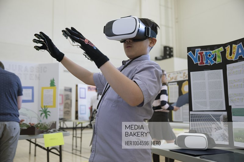 Boy middle school student using virtual reality simulator glasses at science fair