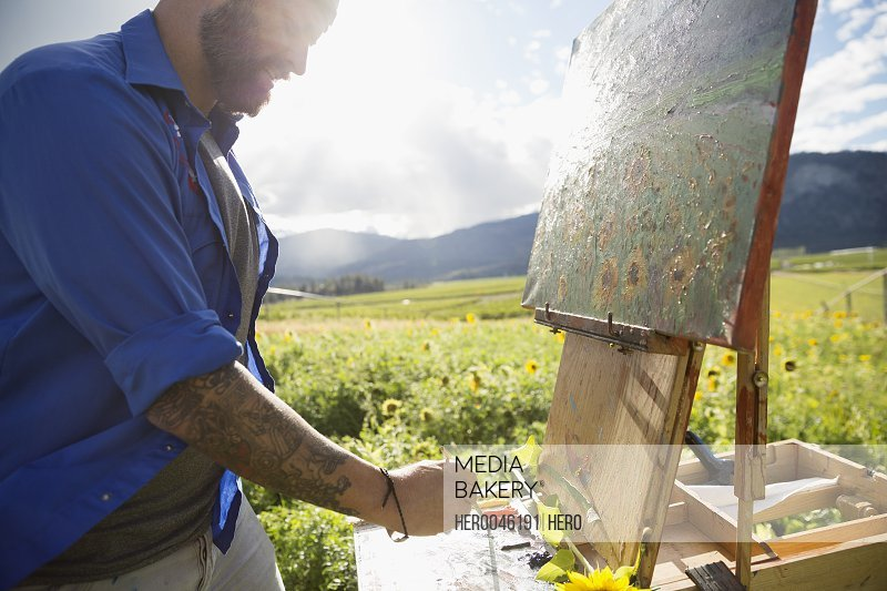 Male painter painting sunflowers in sunny idyllic rural field