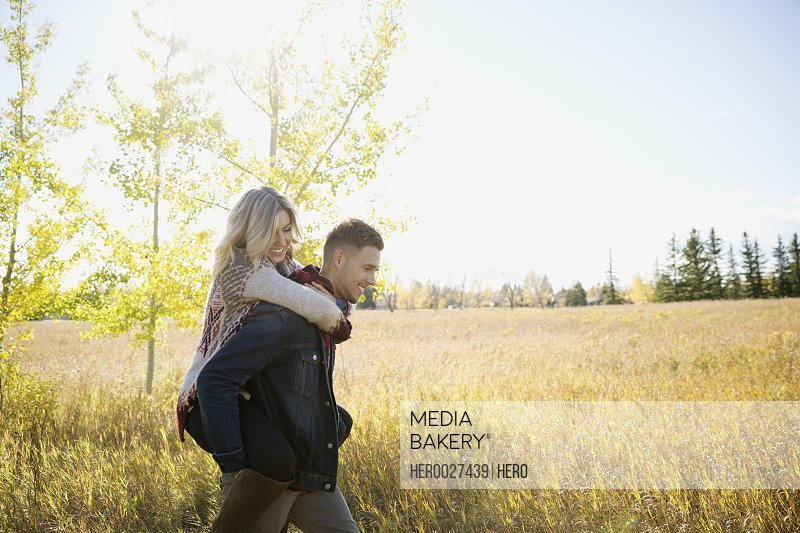 Couple piggybacking in sunny field