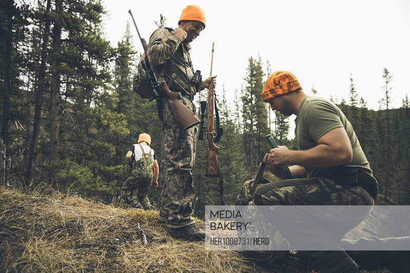Multi-generation male hunters with backpack and hunting rifles in forest
