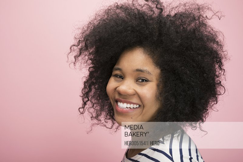 Portrait smiling young woman with curly black hair against pink background
