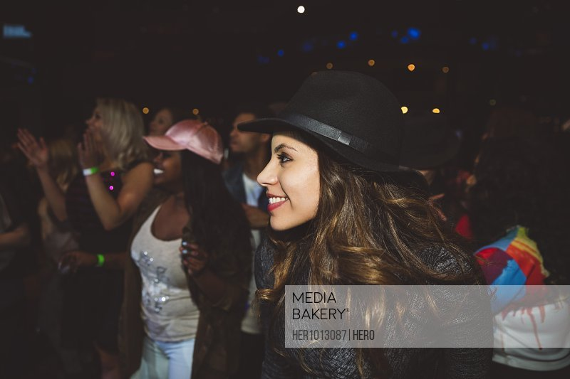 Smiling, confident young female millennial enjoying music concert in nightclub