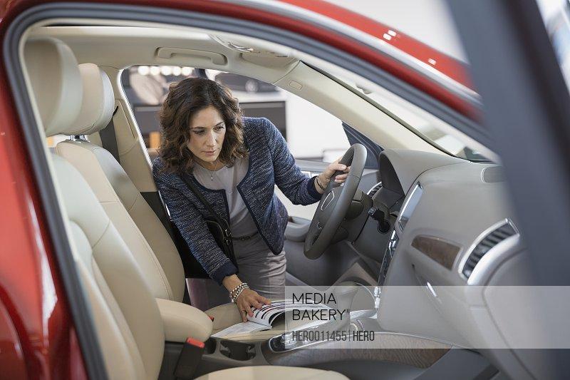 Woman looking inside car in car dealership showroom