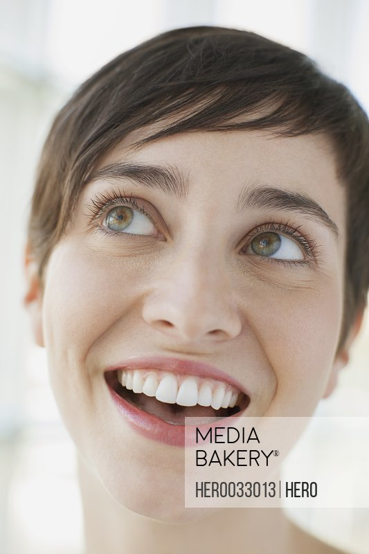 close up of smiling young adult woman looking up