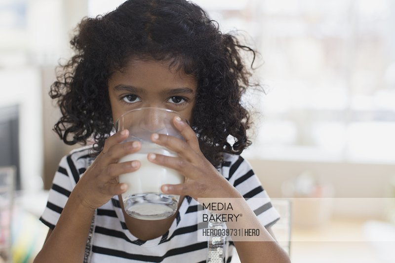 Portrait of young girl drinking milk