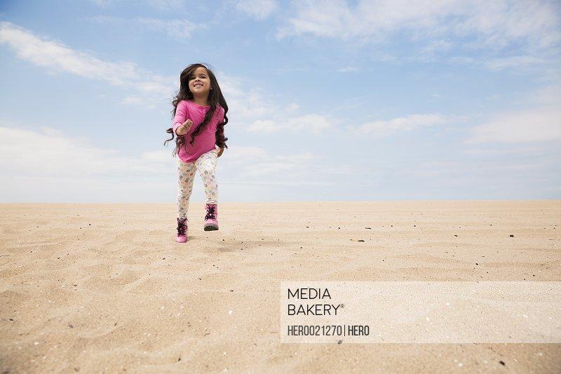 Smiling girl long hair running on beach slope