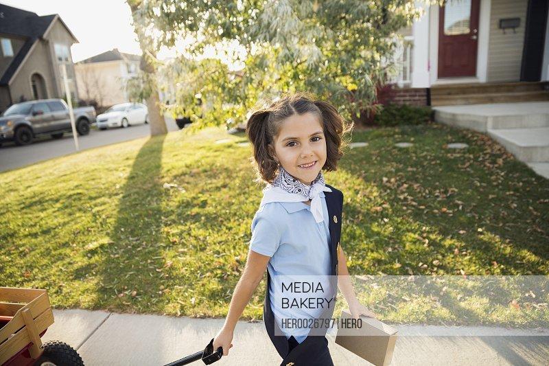 Portrait smiling girl scout selling cookies in neighborhood