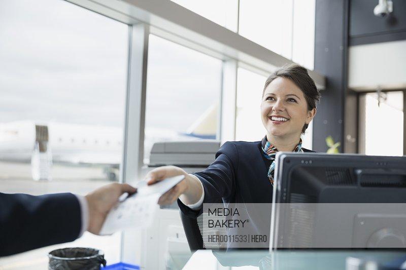 Airport customer service representative giving ticket to traveler