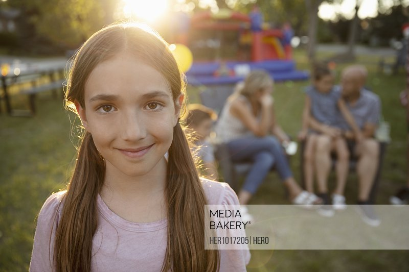 Portrait smiling, confident girl in sunny park with family