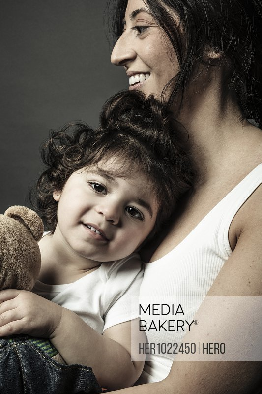 Portrait Latina mother holding cute toddler daughter