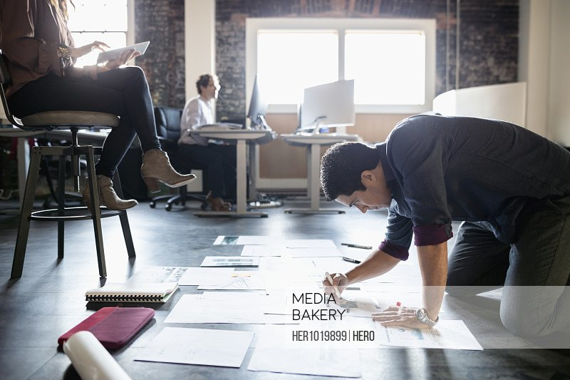 Dedicated creative businessman editing proofs on office floor