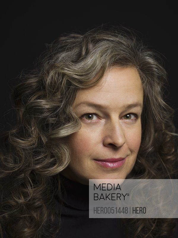 Close up portrait confident woman with curly gray hair against black background