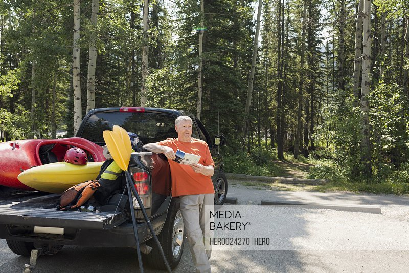 Man holding map at truck with kayaks