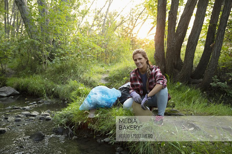 Portrait confident woman volunteering, cleaning up garbage in woods