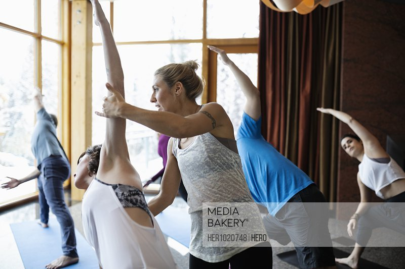 Instructor supporting woman practicing side angle pose in yoga class studio