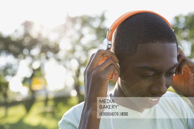 Teenage boy listening to music in park