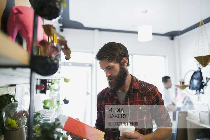 Bearded man with coffee browsing in shop