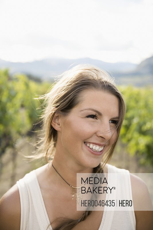 Smiling woman looking away in vineyard