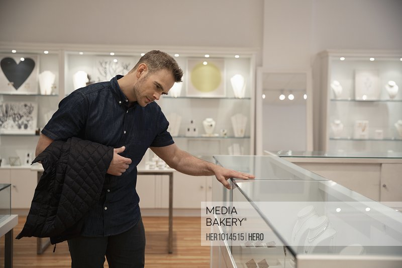 Man shopping for jewelry, looking at display case in boutique