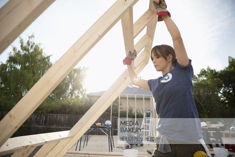 Female volunteer building house