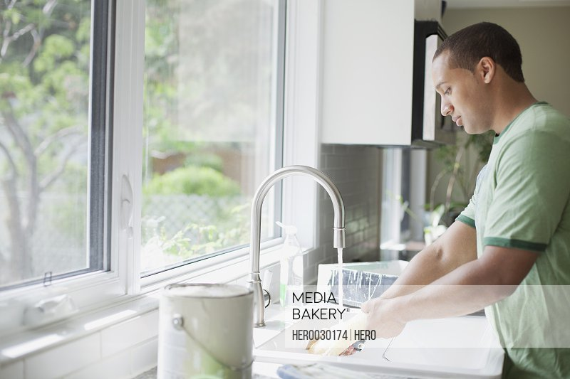 young adult man washing up paint roller