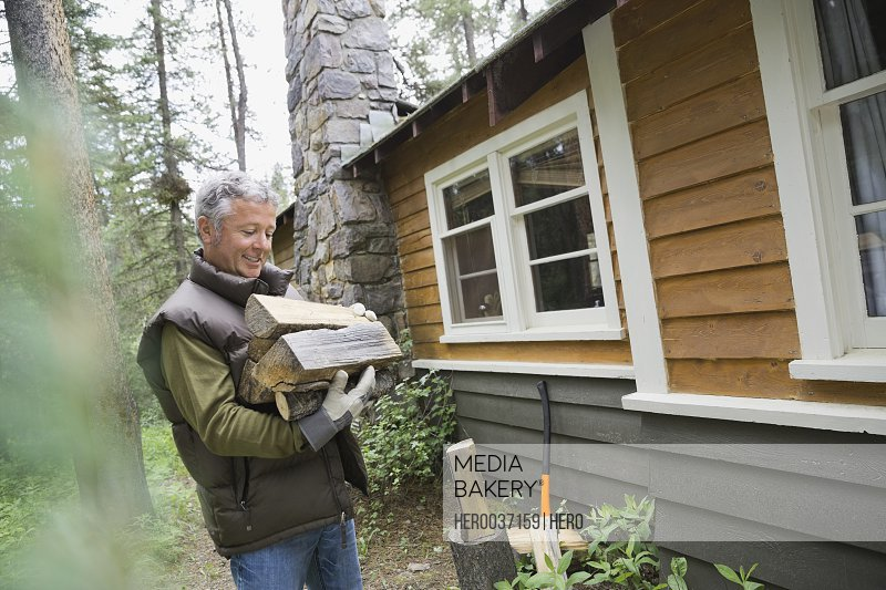 Mature man holding firewood