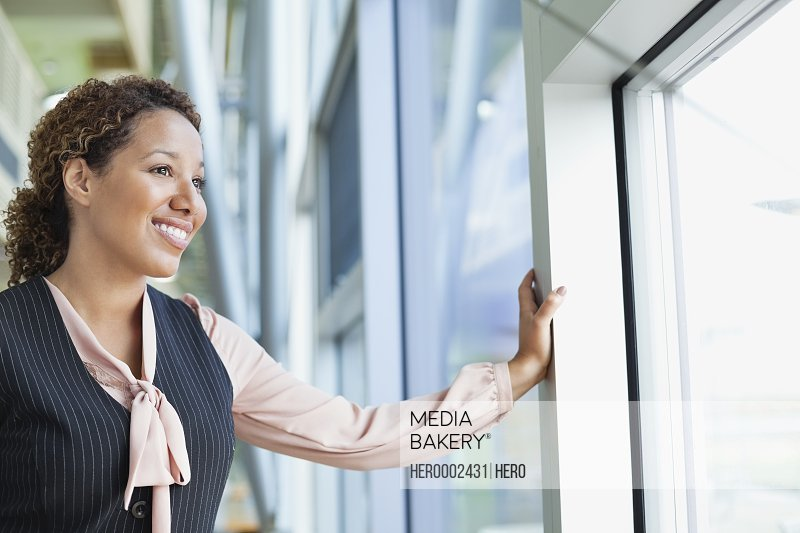 Smiling businesswoman looking out window in office