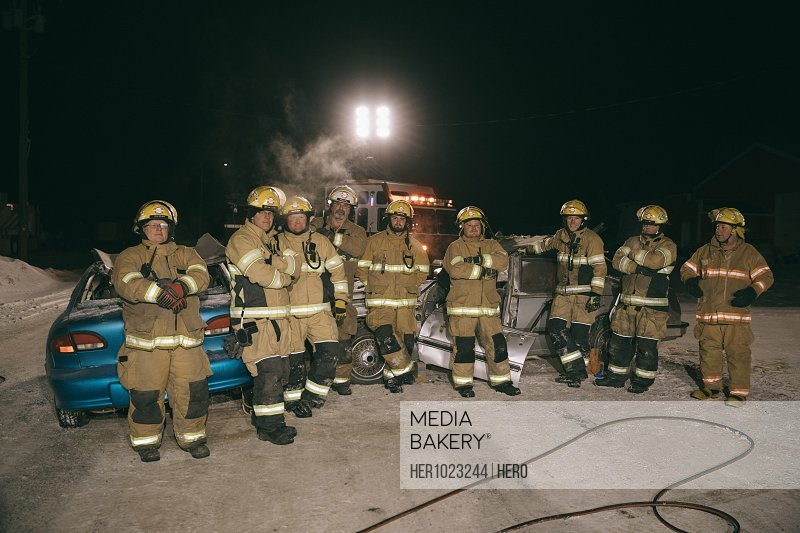 Portrait confident firefighters at scene of car accident