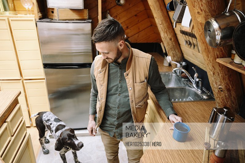 Man with dog drinking coffee in cabin kitchen