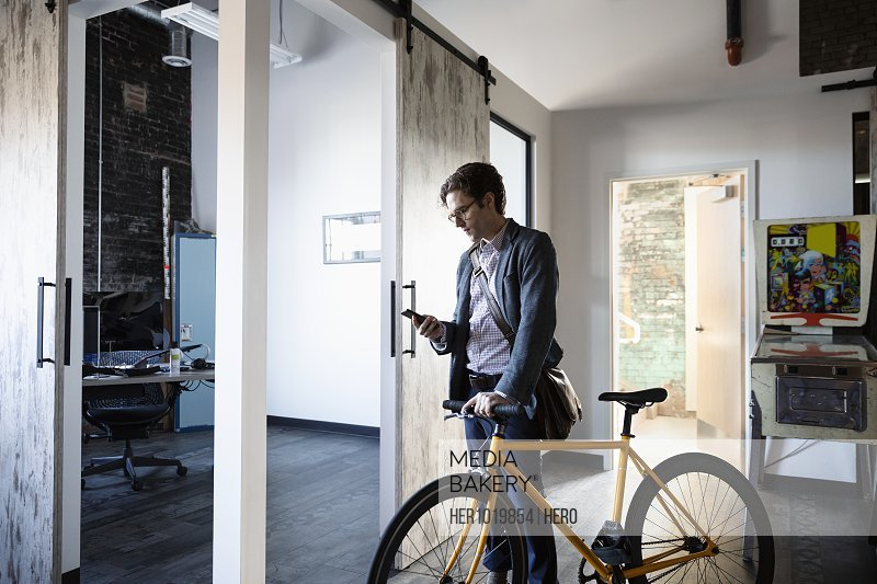Creative businessman with smart phone and bicycle arriving at office