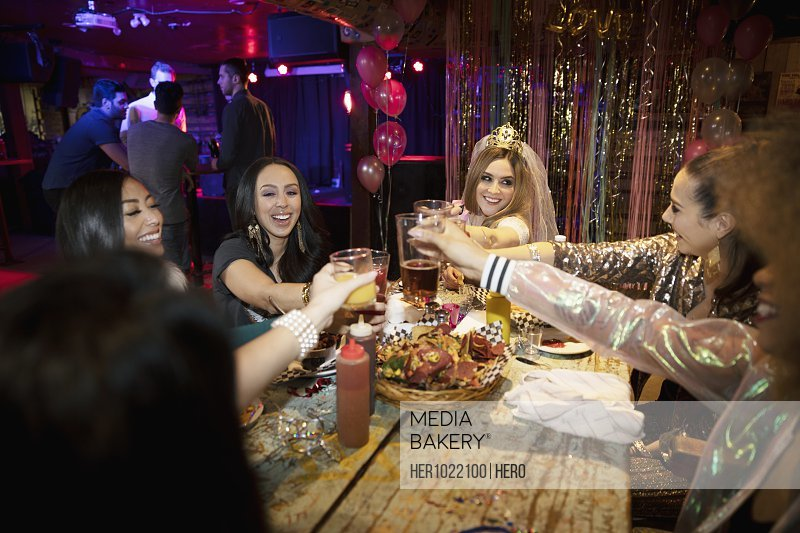 Bachelorette and friends toasting cocktails in nightclub