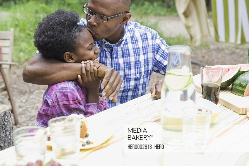 Father kissing daughters forehead outdoors
