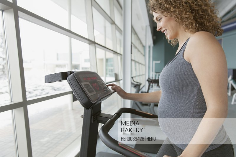 Profile of pretty pregnant woman at fitness center