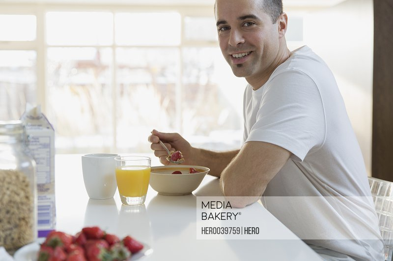 Man at breakfast table with fruit and cereal