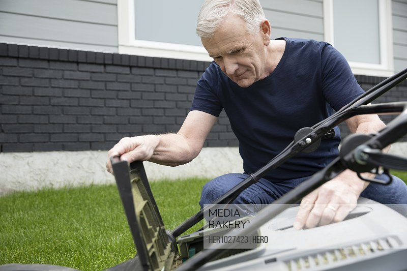 Senior man fixing lawn mower in yard