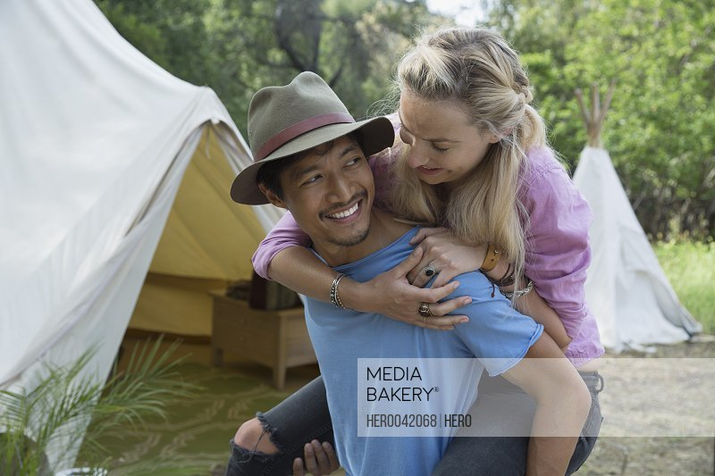 Young couple piggybacking outside camping yurt