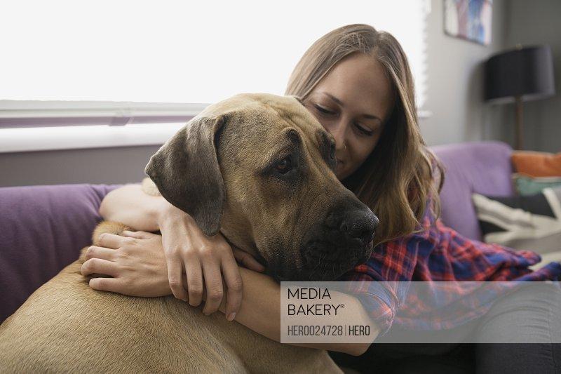 Woman hugging dog on living room sofa