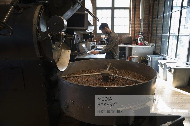 Male coffee roaster using laptop next to coffee roasting machine