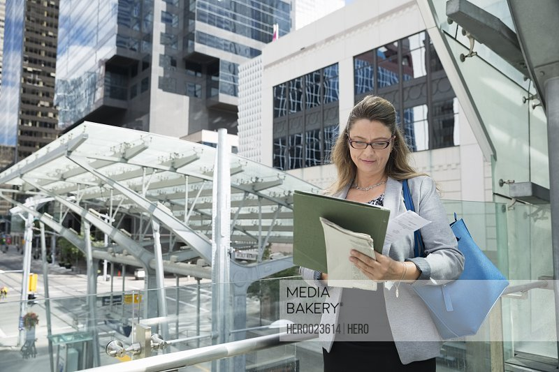 Businesswoman reviewing paperwork in city