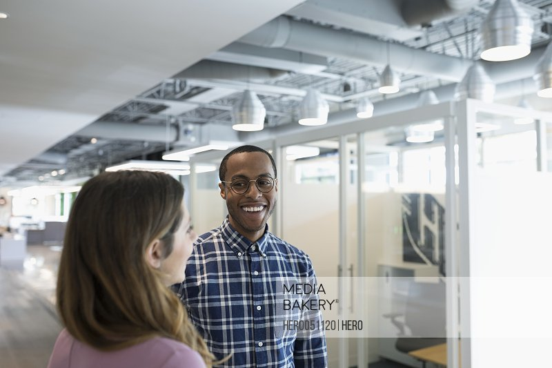 Smiling businessman and businesswoman talking in office corridor