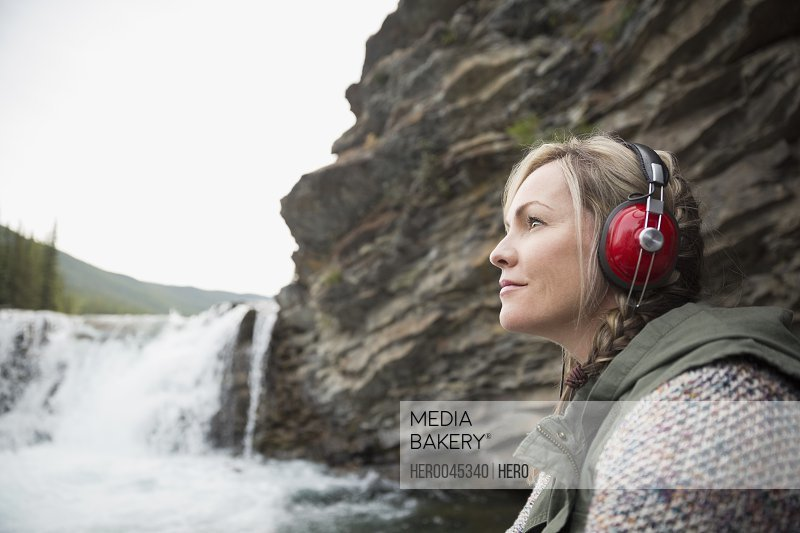 Serene woman listening to headphones with music at waterfall