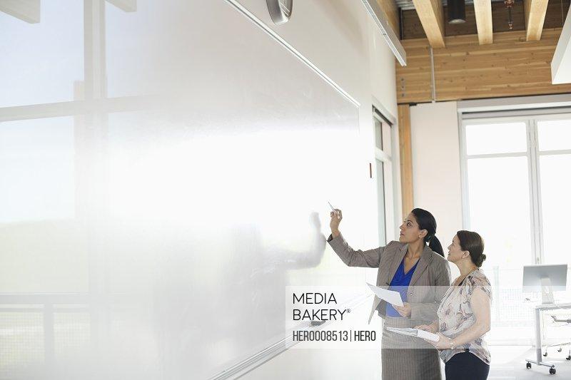 Businesswomen writing on whiteboard