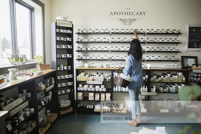 Woman reaching for bottle on shelf apothecary shop