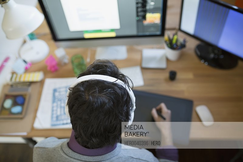 Designer with headphones using graphics tablet at computer